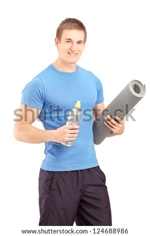 A male holding a bottle of refreshment drink and a mat after an excerise isolated on white background - stock photo