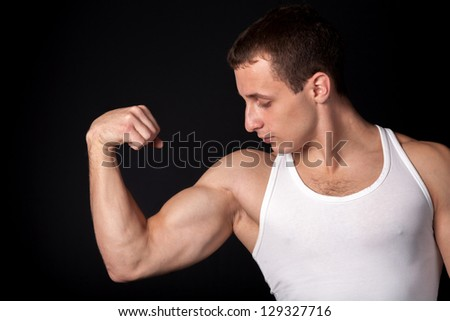 a male in white tank top with strong muscles on black background - stock photo
