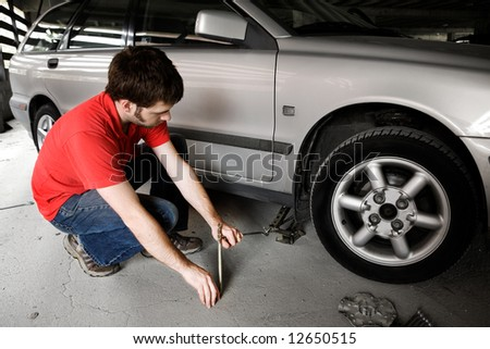 A male jacks up a car in a garage - fixing the wheel - stock photo