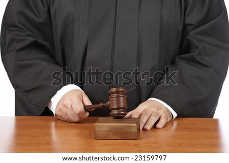 A male judge in a courtroom striking the gavel. Shallow depth of field - stock photo