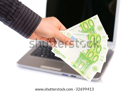 A male man holding in his hand 400 Euro, a laptop in the background.