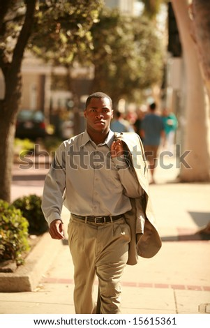 a male model walks towards the camera on a city sidewalk