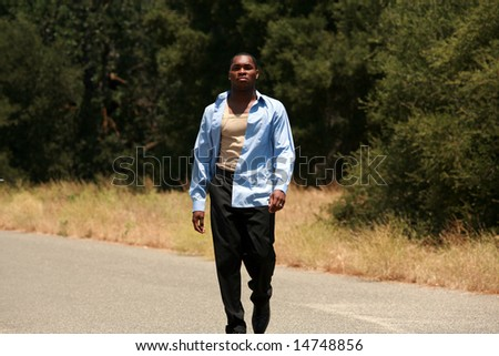 a male model walks towards the camera outside in a park