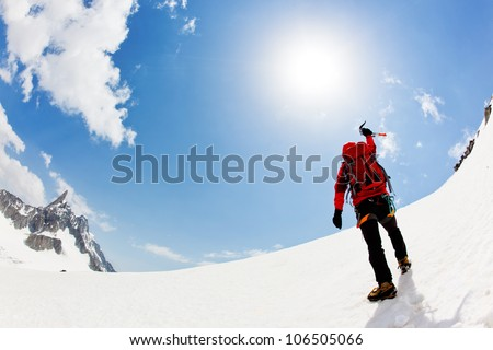 A male mountaineer expresses his joy reaching the summit of a snowed mountain peak. Mont Blanc, Chamonix, France.