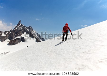 A male mountaineer on the way for reach the summit. Dent du Geant, Mont Blanc, Chamonix, France. - stock photo