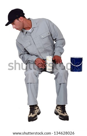 A male painter looking down. - stock photo