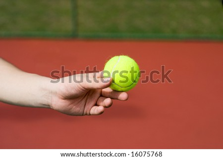 A male player is holding a fresh green tennis ball at the tennis court.