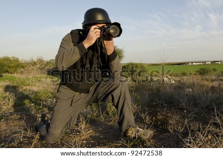 A male press photographer wears a protective helmet and vest and takes photos with a professional camera - stock photo