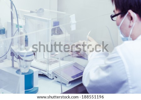 a male researcher doing research in a lab??science test background - stock photo