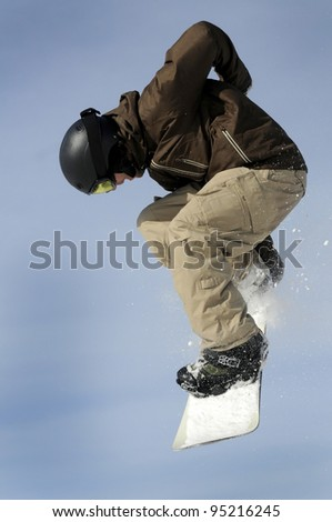 a male snowboarder performing jump against a blue sky