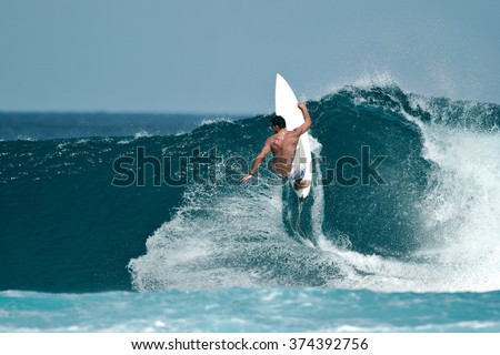 A male surfer executes a radical move on a beautiful ocean wave. - stock photo