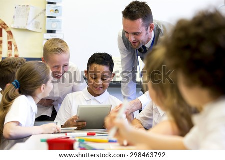 A male teacher sits supervising a group of children who are working on whiteboards and digital tablets.  - stock photo