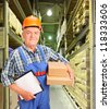 A male worker in uniform holding boxes and clipboard at warehouse - stock photo