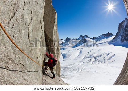 A male young climber along a pitch on the south face of Mont Blanc massif. Petit Capucin, Mont Blanc, France. - stock photo