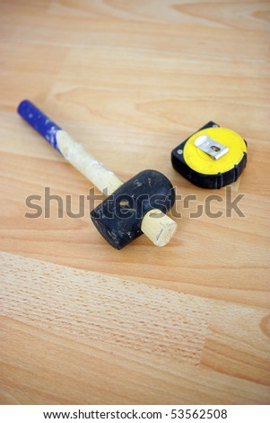 A mallet and a tape measure - stock photo