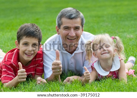 a man, a little girl and a boy are lying on the grass in the park