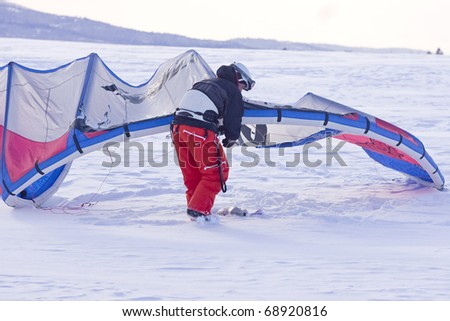 A man adjusts his snow kite before kiting on his snowboard. - stock photo