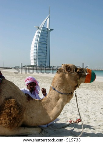 A man and a camel posing in front of the most beautiful hotel in the world in dubai city, UAE - stock photo