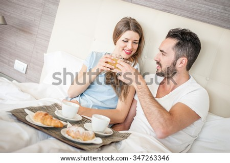 A man and a woman are having breakfast on the bed.  - stock photo