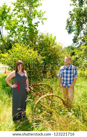 A man and a woman are in an overgrown field with rusted farm equipment.