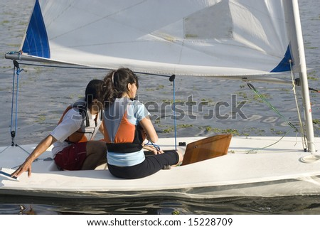A man and a woman are sitting together on a sailboat.  Horizontally framed shot. - stock photo