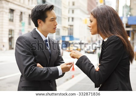 A man and a woman arguing on a city street. - stock photo