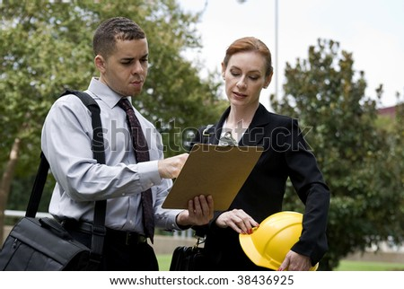 A man and a woman carrying a hardhat, standing outside, and discussing the paperwork on the clipboard the man is holding. - stock photo