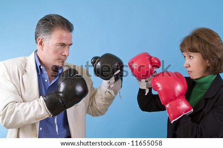 A man and a woman in business suits wearing boxing gloves as if ready to fight. - stock photo