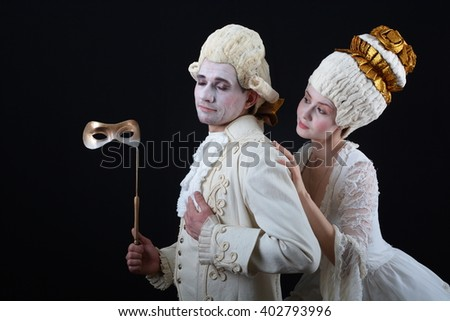a man and a woman in period costume and wigs and holding a theatrical mask - stock photo
