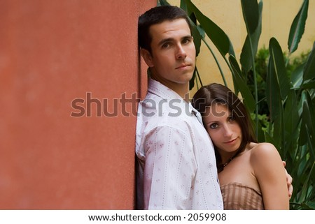 A man and a woman standing at a wall