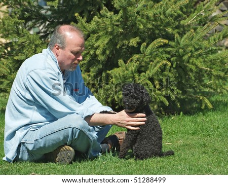 A man and his sweet little poodle playing outside together. - stock photo
