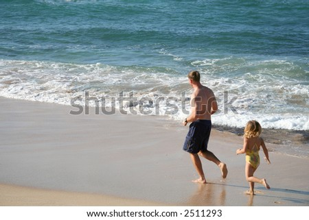 A man and his young daughter running along the beach - stock photo