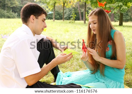 A man and woman make paper cranes - stock photo