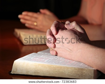 A man and woman (or couple) praying together at a table with their Holy Bibles open under their hands (focus on man's foreground hands). - stock photo