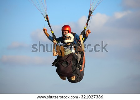 A man and woman paragliding - stock photo