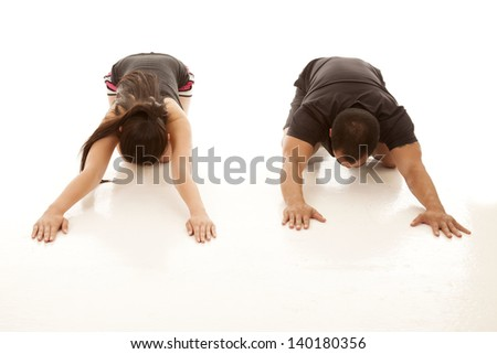 A man and woman relaxing and doing a stretch after working out. - stock photo