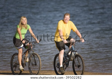 A man and woman riding their bikes on a beach by the water.
