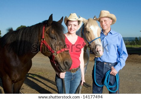 A man and woman stand smiling with their horses. - horizontally framed - stock photo
