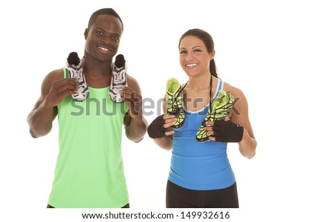 a man and woman with smiles on their faces holding on to their running shoes. - stock photo