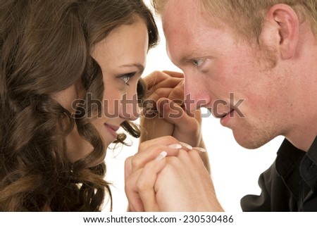 a man and woman with their hands together looking at each other. - stock photo