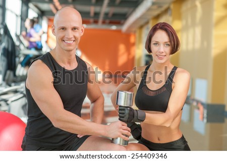 A man and woman working out at the gym with dumbbell - stock photo