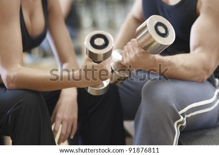 A man and woman working out at the gym with dumbbell weights - stock photo