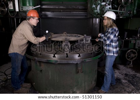 A man and woman working together on a project on a machine.  The man is saying something funny they are laughing.
