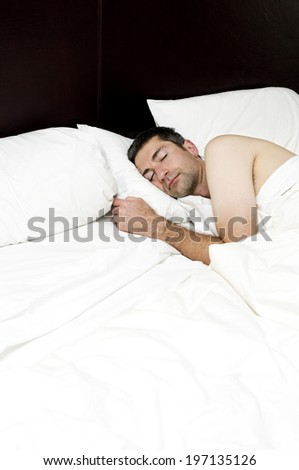 A man asleep on a large bed with big pillows.