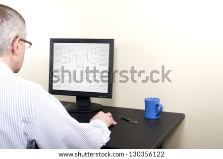 A man at a computer screen doing his March Madness basketball tournament bracket.