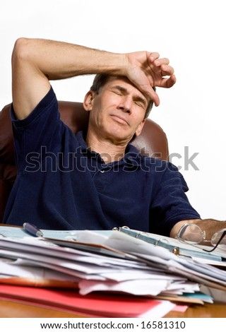 A man at his desk worrying how he will pay the bills - stock photo