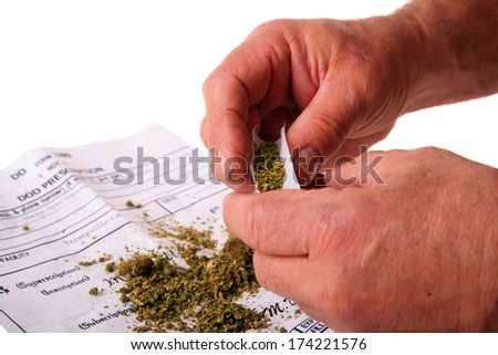 "A man attempts to roll a ""Joint"" out of Marijuana on his new Prescription for Legal Pot. Many States are considering legalizing pot as medicine.  - stock photo"