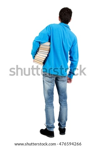 A man carries a heavy pile of books. back view. curly-haired student in a blue warm jacket standing with a stack of books.