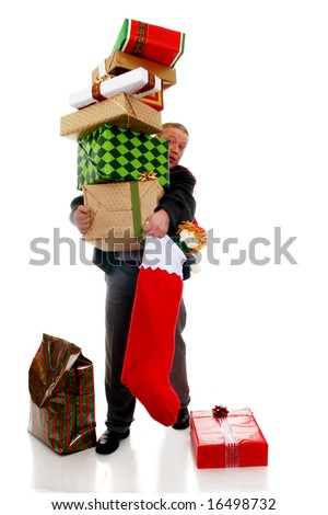 A man carrying a precarious stack of colorfully wrapped Christmas gifts.