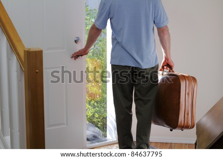 A man carrying a suitcase about to walk out the front door of his house to travel. - stock photo